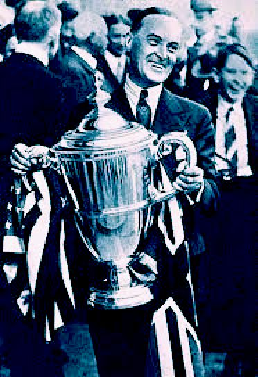 Malcolm Campbell holding a large winners cup